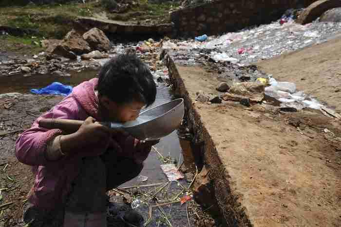 Ένα παιδί πίνει μολυσμένο νερό στην περιοχή Fuyuan County, στην επαρχία Γιουνάν της Κίνας