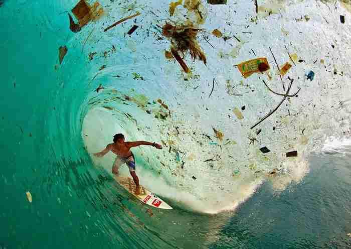 Σέρφερ κάτω από ένα κύμα γεμάτο σκουπίδια (Ιάβα, Ινδονησία - το πολυπληθέστερο νησί στον κόσμο)