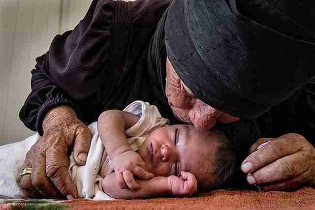 Μια ηλικιωμένη πρόσφυγας φιλάει το 10 μόλις ημερών εγγονάκι της.