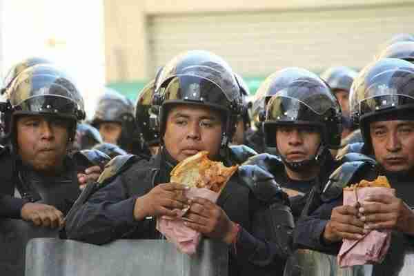 Μεξικανοί αστυνομικοί κάνουν ένα διάλειμμα για φαγητό κατά τη διάρκεια διαδηλώσεων.