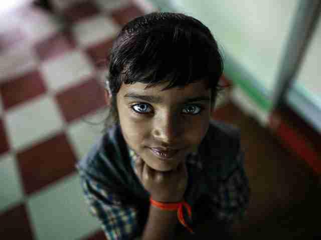 Ένα κορίτσι που πάσχει από διαταραχές ακοής και ομιλίας ποζάρει χαμογελαστό στην κάμερα.