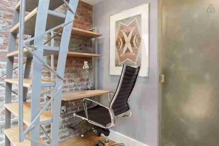 Κάτω από τη σκάλα υπάρχει ένα γραφείο με ενσωματωμένα ράφια στους τοίχους.
