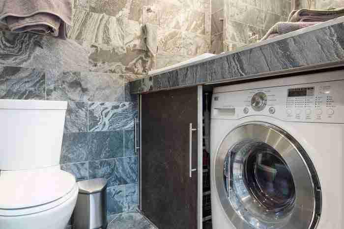 Κρυμμένο δίπλα στην τουαλέτα βρίσκεται ένα πλυντήριο.