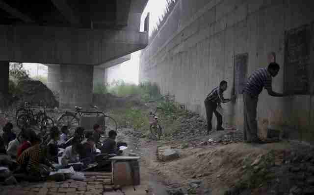 Άστεγα και εξαθλιωμένα παιδιά που ζουν στο Νέο Δελχί, στην Ινδία, εκπαιδεύονται δωρεάν από δύο εθελοντές εκπαιδευτικούς.