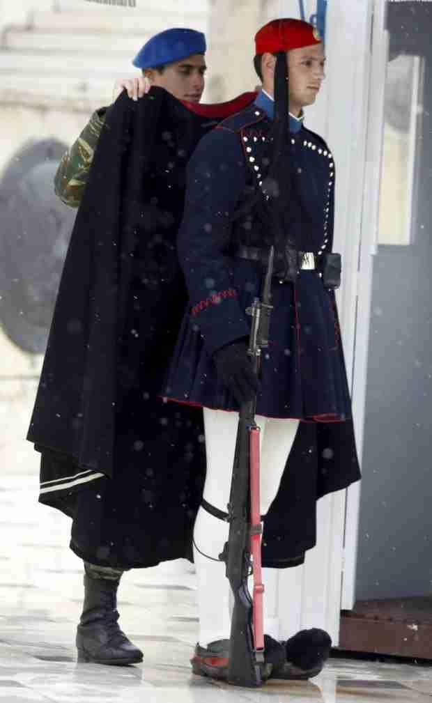 Ένας αξιωματικός της Προεδρικής Φρουράς, φοράει μια κάπα στον ακίνητο τσολιά, προκειμένου να τον προφυλάξει από το κρύο.