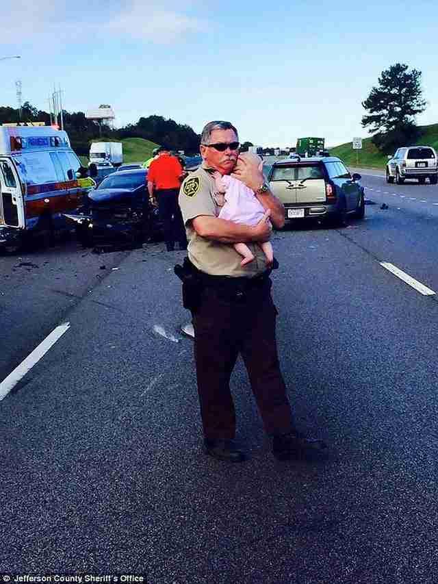 Αστυνομικός αγκαλιάζει για να ηρεμήσει ένα μωρό μετά από τροχαίο ατύχημα