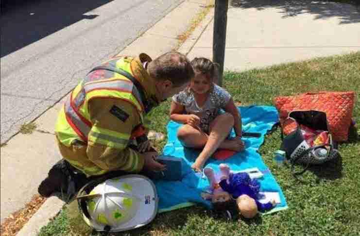 Ένας πυροσβέστης προσπαθεί να αποσπάσει την προσοχή ενός παιδιού από το φλεγόμενο σπίτι του