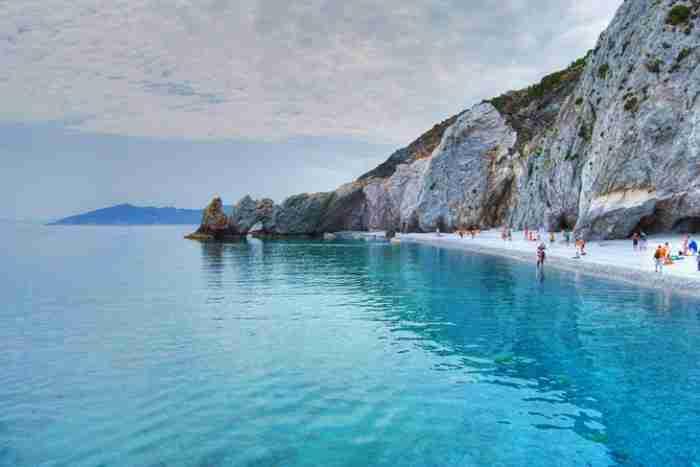 """Η απομακρυσμένη ελληνική παραλία που λατρεύουν οι φωτογράφοι. Ολόλευκα βότσαλα, νερά """"πισίνας"""" και μια εντυπωσιακή πέτρινη αψίδα"""