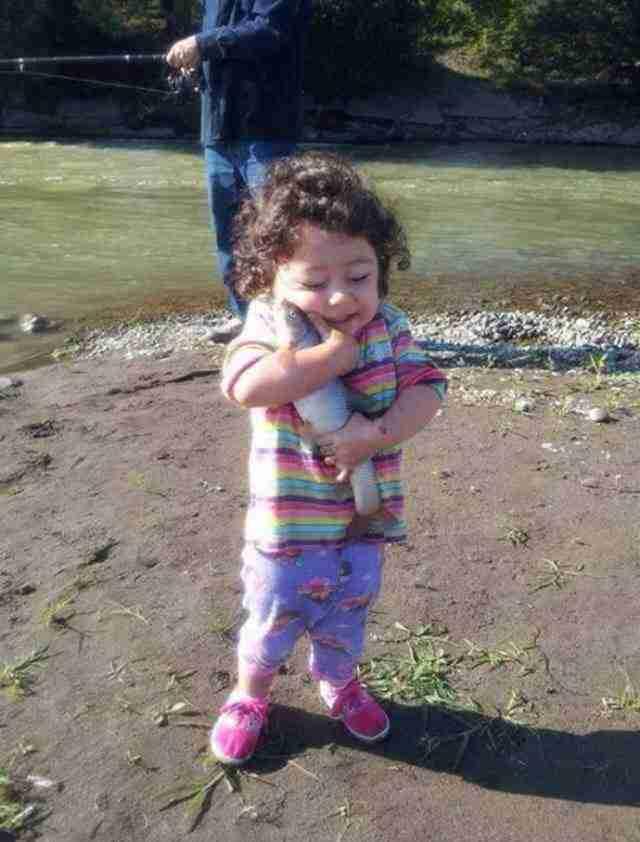 Αυτό το μικρό κορίτσι με την όμορφη καρδιά που πήρε το ψάρι που μόλις έπιασε ο μπαμπάς της και το αγκάλιασε με αγάπη.