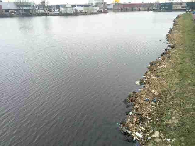 """""""Ένα τμήμα της όχθης του ποταμού καλύπτεται με πλαστικά μπουκάλια αλλά και άλλα (κυρίως) πλαστικά σκουπίδια."""""""