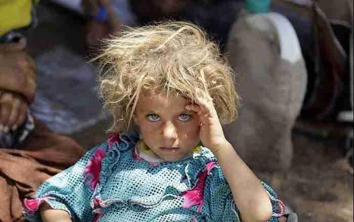 Ένα κορίτσι Yazidi κοιτάζει έντονα την κάμερα