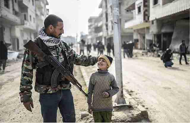 Ένας κούρδος μαχητής περπατά με το παιδί του στους δρόμους του Kobani, στη Συρία,