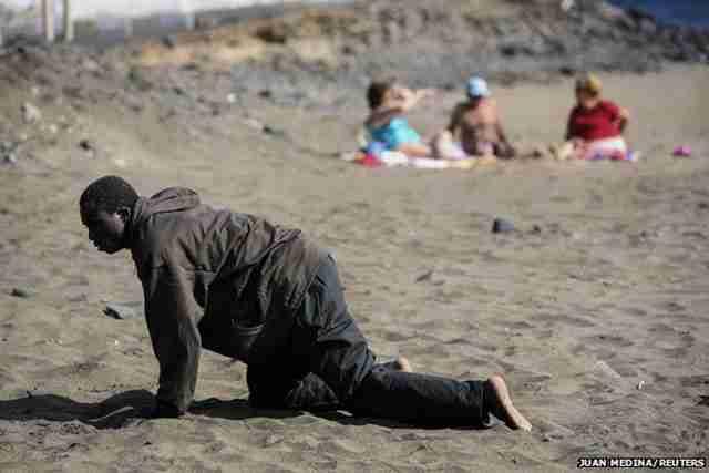 Εξαντλημένος Αφρικανός πρόσφυγας βγαίνει σε μια παραλία των Καναρίων Νήσων.