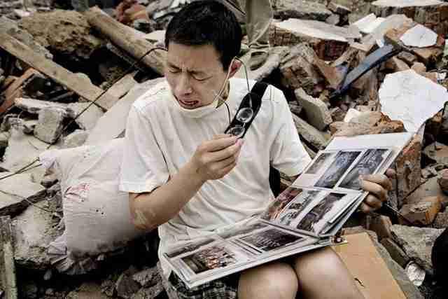 Ένας επιζών βρίσκει ένα φωτογραφικό άλμπουμ με τις αγαπημένες του αναμνήσεις στα ερείπια του σπιτιού του μετά από σεισμό στη Σιτσουάν, Κίνα.