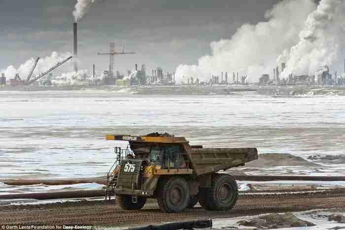 Ένα τεράστιο φορτηγό μεταφέρει ένα φορτίο πετρελαιοφόρα άμμος για επεξεργασία.